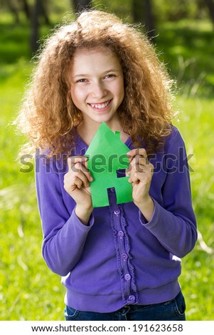Closeup portrait little, cute, happy, smiling, adorable girl with new toy small house in hands isolated green grass, trees outdoor background. Positive emotions, facial expressions, joyful family life - stock photo