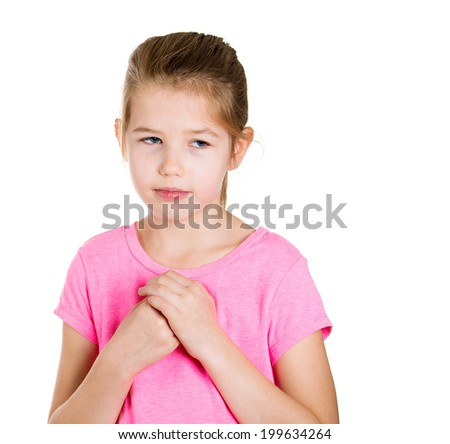 Closeup portrait little, cute, shy girl in pink t-shirt hands on chest isolated white background in studio. Human face expression, emotion, reaction life perception, worries, anxiety social situation  - stock photo