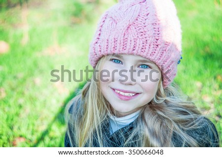 Closeup portrait  little girl in pink hat smile against green grass