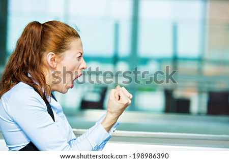 Closeup portrait mad angry, upset, hostile young businesswoman, worker, furious yelling hands, fists in air isolated background corporate office windows. Negative emotions, facial expression, reaction - stock photo