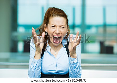 Closeup portrait mad angry, upset, hostile young businesswoman, worker, furious yelling hands in air, isolated background corporate office windows. Negative emotions, facial expression, reaction - stock photo
