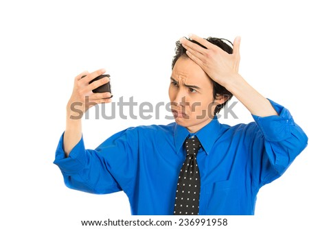 Closeup portrait man looking in mirror feeling head surprised shocked he is losing hair receding hairline isolated on white background. Negative facial expression emotion feeling reaction - stock photo