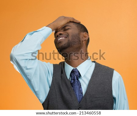 Closeup portrait man with sad expression, hand on face, isolated orange background. Human emotions, body language, life perception. Duh moment. - stock photo