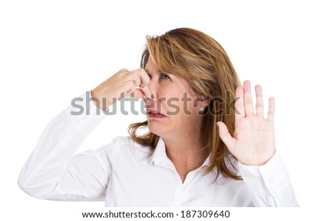 Closeup portrait, mature beautiful, unhappy woman who covers her nose, looks at you, something stinks, very bad smell, situation, isolated white background. Human facial expressions, emotions - stock photo