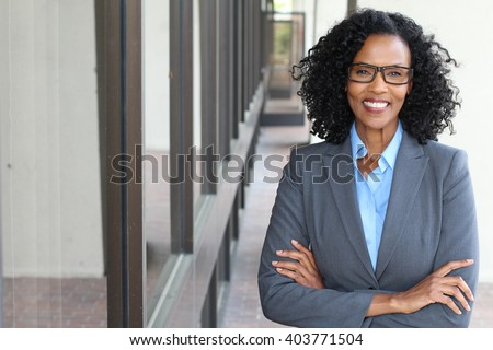 Closeup portrait, mature professional, beautiful confident woman wearing a power suit, friendly personality, smiling isolated indoors office background. Positive human emotions - stock photo