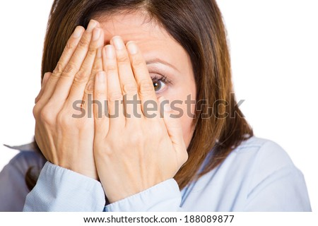 Closeup portrait, mature, scared, terrified, horrified shocked woman peeking through covered hand, can't believe what she sees, isolated white background. Negative emotion facial expression feelings.