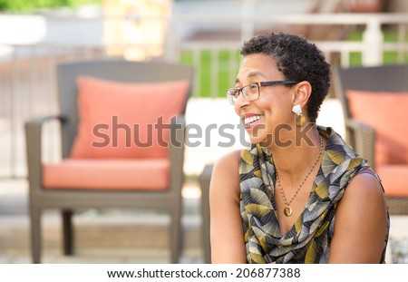 Closeup portrait, mature woman with glasses sitting and smiling, isolated outdoors background with patio furniture - stock photo