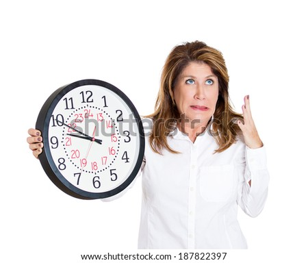 Closeup portrait mature, woman, worker, holding clock looking anxiously, pressured by lack, running out of time, isolated white background. Human face expression, emotion, reaction, corporate life