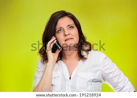 Closeup portrait middle aged angry business woman, corporate employee talking on cell phone, having unpleasant conversation, isolated green background. Negative emotions, facial expressions, reaction - stock photo