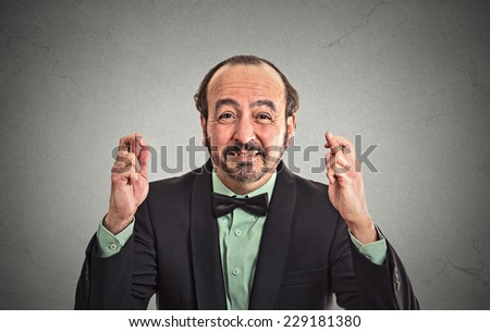 Closeup portrait middle aged funny guy business man crossing fingers wishing hoping for best miracle isolated black grey wall background. Positive human emotion facial expression feeling attitude - stock photo
