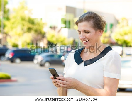 Closeup portrait middle aged, happy, smiling woman texting on her smart phone, isolated outdoor parking lot background. Communication concept. Positive facial expressions, emotion, feelings, good news - stock photo