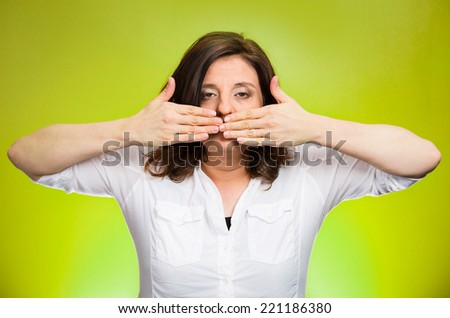 Closeup portrait middle aged woman covering closed mouth. Speak no evil concept, isolated green background. Negative human emotion facial expressions, sign, symbol. Media news coverup, censorship  - stock photo