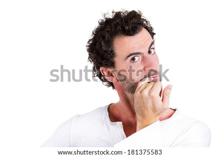 Closeup portrait nerdy, shy, confused young guy, scared, shocked, restless man biting his nails looking at you with craving for something isolated white background. Human emotions, facial expressions