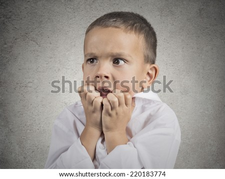 Closeup portrait nervous anxious stressed child boy biting fingernails looking anxiously craving something, afraid having panic attack isolated grey wall background. Negative emotion facial expression - stock photo