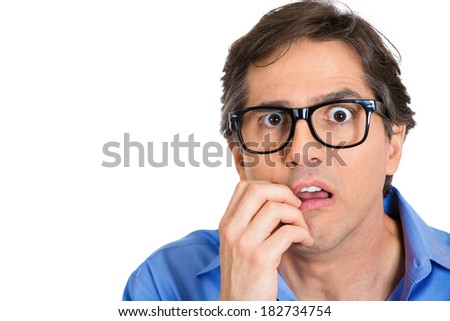 Closeup portrait nervous, stressed young nerdy guy, man with eye glasses biting fingernails looking anxiously craving something isolated white background. Negative emotion expression feeling, reaction - stock photo
