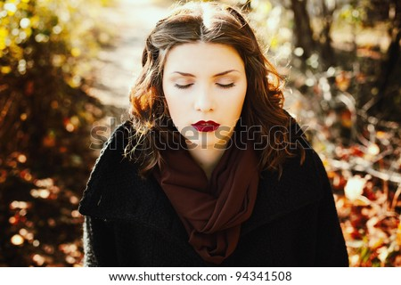 Closeup portrait of a attractive girl with her eyes closed, amid yellow leaves - stock photo