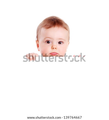 Closeup portrait of a baby boy hiding behind the blank board