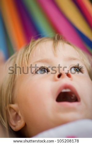 Closeup portrait of a baby girl looking up - stock photo