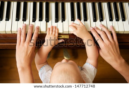 Closeup portrait of a baby learning to play piano with mother - from above - stock photo