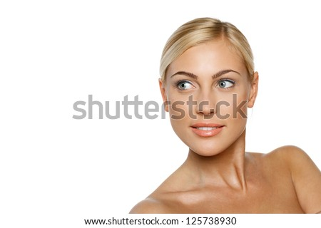 Closeup portrait of a beautiful blond female model on white background looking to the side at blank copy space