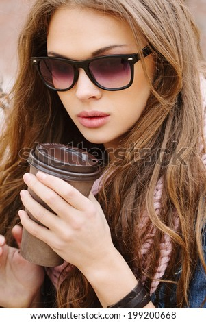 Closeup portrait of a beautiful brunette girl wearing sunglasses, holding drink in her hands. Looking at camera. Warm sunny day. Outdoors