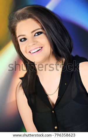 Closeup portrait of a beautiful brunette teen with colorful lights in the background.