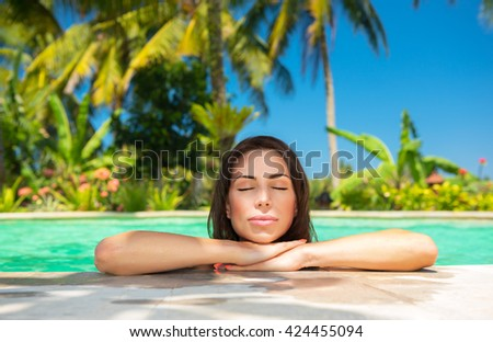 Closeup portrait of a beautiful calm female with closed eyes enjoying bright warm sun light, relaxation in a swimming pool, luxury summer vacation - stock photo