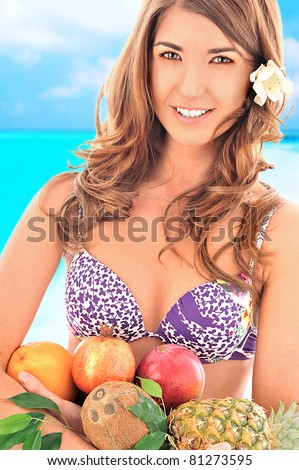 Closeup portrait of a beautiful cheerful woman with flower in her hair holding fruits in her arms, wearing swimsuit.