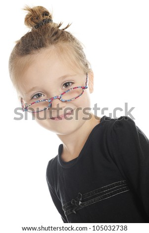 Closeup portrait of a beautiful elementary girl looking over the top of her colorful glasses and with her hair in a bun. On a white background. - stock photo