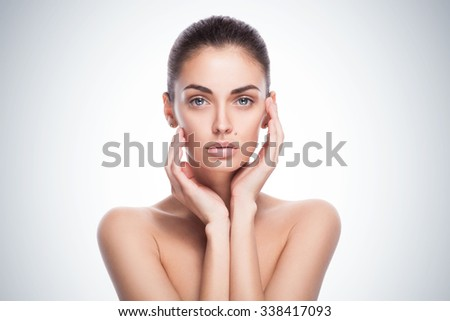 closeup portrait of a beautiful female model with her hands near face - isolated on blue gradient background