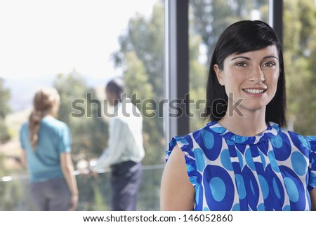 Closeup portrait of a beautiful female with blurred colleagues in background - stock photo