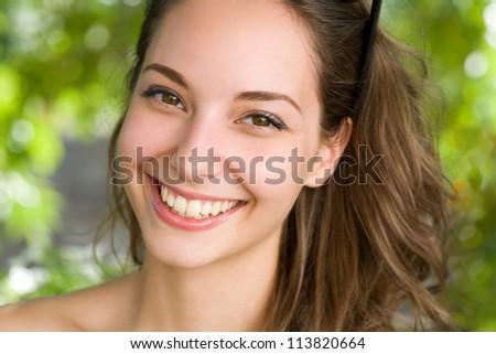 Closeup portrait of a beautiful  friendly young brunette woman. - stock photo