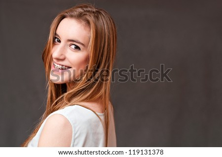 closeup portrait of a beautiful girl wearing braces, on the side - stock photo