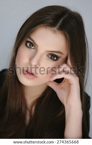 Closeup portrait of a beautiful girl with smoky eyes makeup and dark hair looking at camera