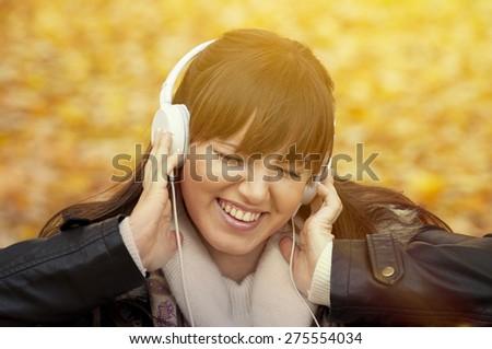 Closeup portrait of a beautiful happy woman listening to music  - stock photo