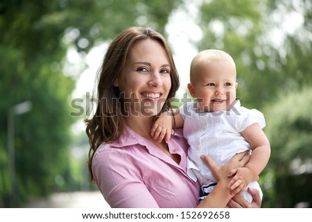 Closeup portrait of a beautiful mother with smiling baby outdoors - stock photo