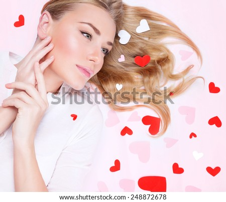 Closeup portrait of a beautiful romantic woman lying down on pink  background, many little red hearts on blond hair, Valentine's day concept - stock photo