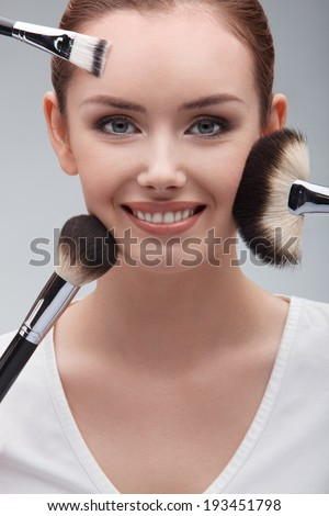 closeup portrait of a beautiful smiling woman with brushes applying makeup on her face - stock photo