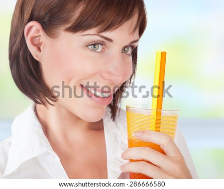 Closeup portrait of a beautiful woman drinking juice at home,  enjoying refreshing citrus beverage, healthy lifestyle and organic nutrition - stock photo