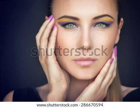 Closeup portrait of a beautiful woman face over dark background, gorgeous model with colorful stylish makeup, fashion look, luxury beauty salon - stock photo