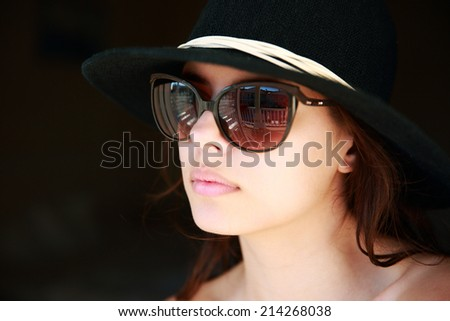 Closeup portrait of a beautiful woman in hat and sunglasses
