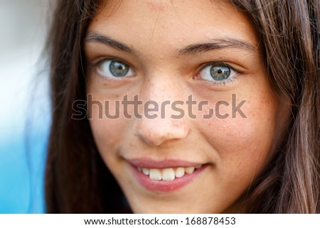 closeup portrait of a beautiful woman looking at camera and smiles