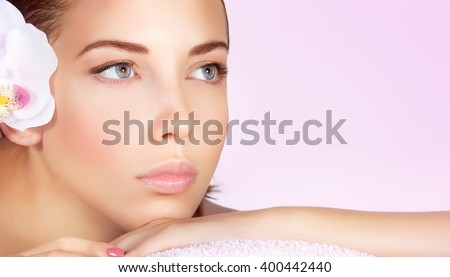 Closeup portrait of a beautiful woman, perfect face with no makeup makeup, female lying down on massage table white orchid flower in hair, enjoying day spa, shot over pink background with copy space - stock photo