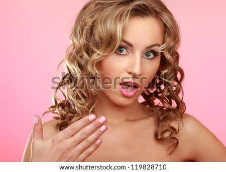 Closeup portrait of a beautiful woman's face, isolated on pink - stock photo