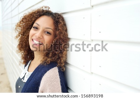Closeup portrait of a beautiful woman with curly hair smiling outdoors - stock photo