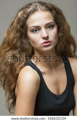 Closeup portrait of a beautiful young brunette woman with natural makeup, perfect skin and gorgeous curly hair - stock photo