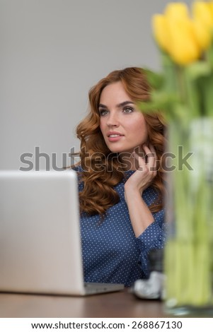 Closeup portrait of a beautiful young redhead woman working using laptop at her desk at office - stock photo