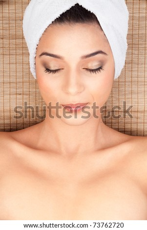 closeup portrait of a beautiful, young woman, at a spa, lying on her back on a bamboo mat, with a towel in her head. she is smiling and her eyes closed. - stock photo