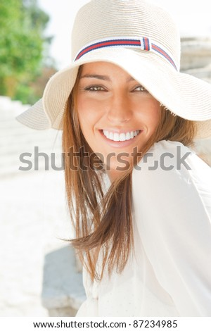Closeup portrait of a beautiful young woman having a happy thought outdoor in summer park looking at camera - stock photo