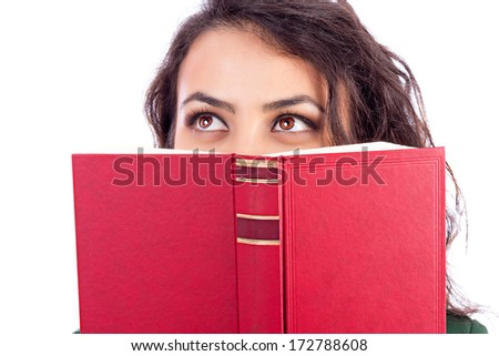 Closeup portrait of a beautiful young woman holding a book in front of her face over white background